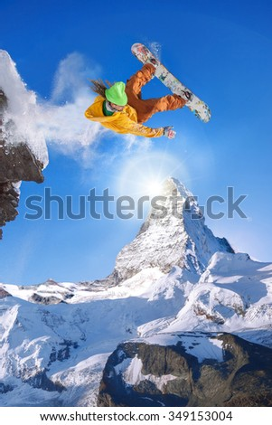 Snowboarder jumping against Matterhorn peak in Switzerland - stock photo