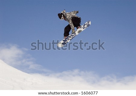 snowboarder jumping high in the air while performing a grab - stock photo