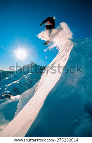 Snowboarder jumping off a cliff off piste, backlit by the sun on a sunny day in Donner Pass, California, USA. - stock photo