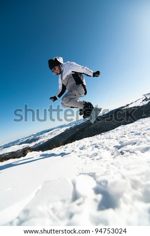 Snowboarder jumping on blue sky background and lots of snow