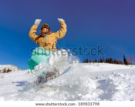 Snowboarder jumping through air with deep blue sky in background - stock photo