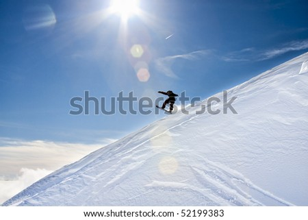 Snowboarder jumps down an incline of the Mountain on a bright, sunny day with blue skies.