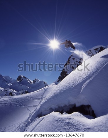 Snowboarder jumps high in dramatic mountain scene with white snow and clear blue sky.