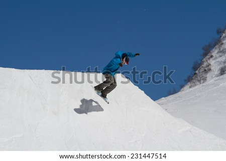 Snowboarder jumps in Snow Park,  mountain ski resort. - stock photo