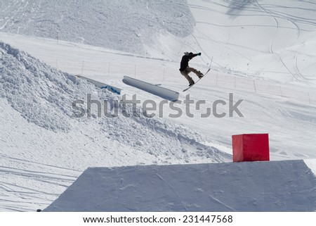 Snowboarder jumps in Snow Park,  mountain ski resort.