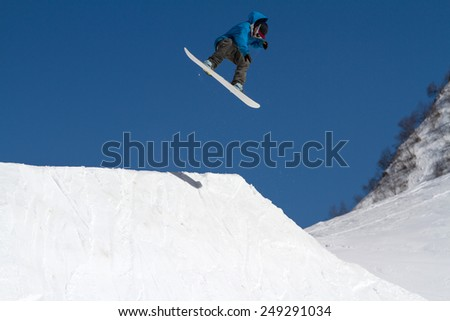 Snowboarder jumps in Snow Park,  mountain ski resort