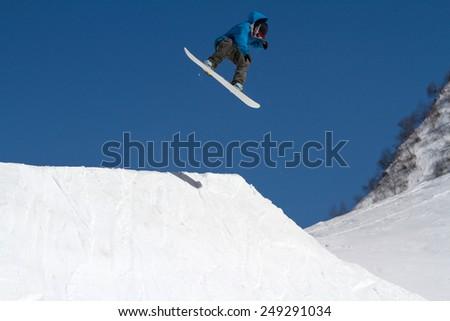 Snowboarder jumps in Snow Park,  mountain ski resort  - stock photo
