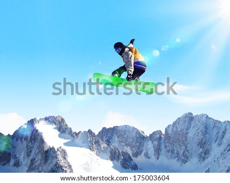 Snowboarder making jump high in clear sky
