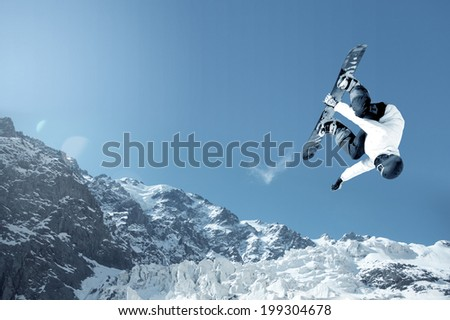 Snowboarder making jump high in clear sky - stock photo