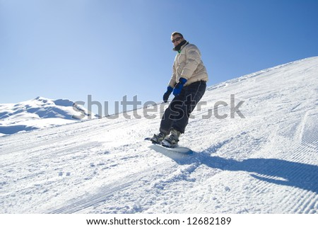 Snowboarder on a mountain in a bright sunny day