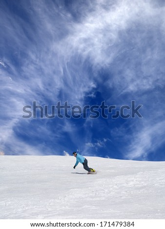 Snowboarder on off-piste ski slope and blue sky with clouds  - stock photo