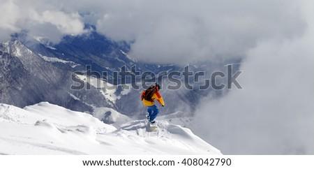 Snowboarder on off-piste slope an mountains in fog. Caucasus Mountains, Georgia, ski resort Gudauri. - stock photo