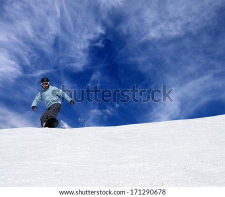 Snowboarder on off piste slope and blue sky with clouds - stock photo