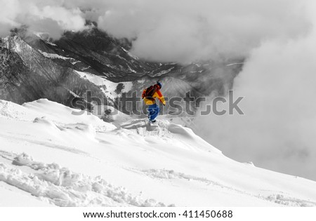 Snowboarder on off-piste slope and mountains in fog. Caucasus Mountains, Georgia, region Gudauri. Selective color. - stock photo