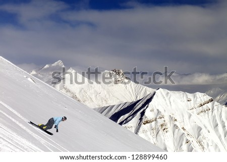 Snowboarder on off-piste slope in mountains - stock photo