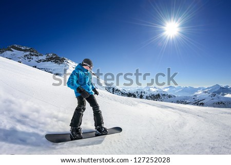 Snowboarder on piste in high mountains - stock photo