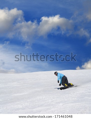 Snowboarder on ski slope at nice sunny day - stock photo