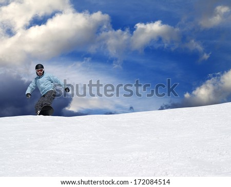Snowboarder on ski slope in winter mountains - stock photo