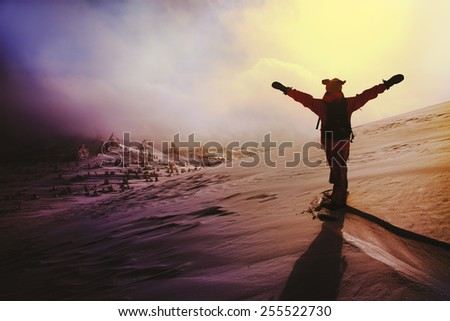Snowboarder on the mountain with his arms raised - stock photo