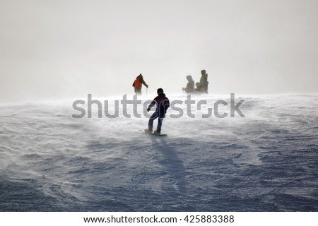 Snowboarder on top of beginner slope on hazy day  - stock photo