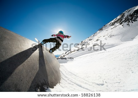 Snowboarder on wall ride with blue sky background - stock photo