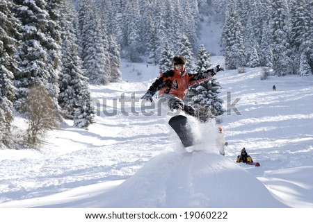 Snowboarder pull-up a sweet grab off a jump - stock photo