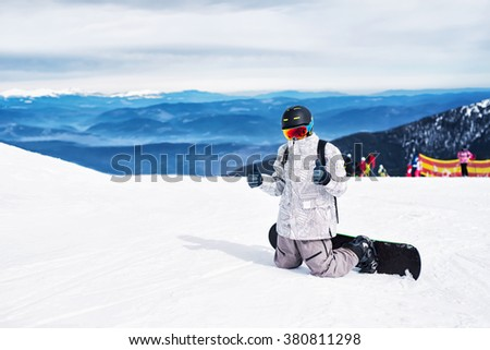 Snowboarder ready for slope showing thumbs up. - stock photo