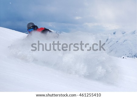 Snowboarder riding fast on a dry snow on freeride slope.
