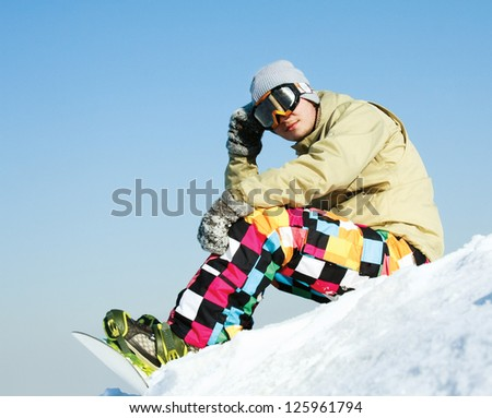 Snowboarder sitting on a ski slope - stock photo