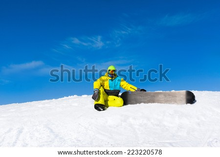 snowboarder sitting on snow mountain slope copy space blue sky - stock photo