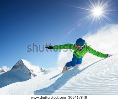 Snowboarder skiing in high mountains at beautiful sunny day. Clear weather and sky, prepared snow / piste. - stock photo