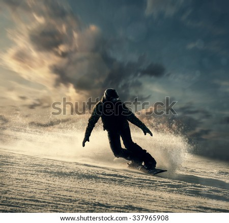 Snowboarder slides down the snowy hill - stock photo