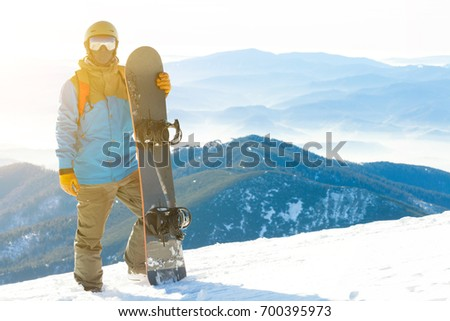 Snowboarder standing next to snowboard thrusted into snow with beautiful scenery with sun-set on background