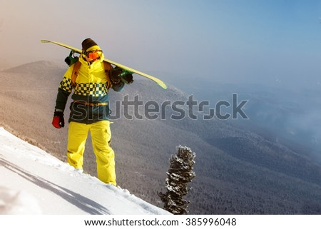 Snowboarder stands on the slope on mountains backdrop. Sheregesh resort, Siberia, Russia - stock photo