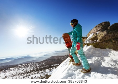 Snowboarder stands on valley and mountains backdrop. Space for text. Sheregesh resort, Siberia, Russia