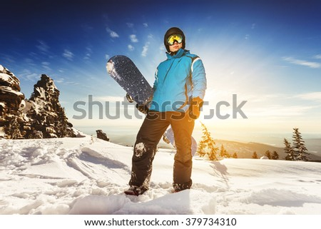 Snowboarder stands with snowboard in sunset light. Sheregesh resort, Siberia, Russia  - stock photo