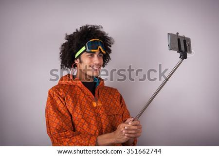snowboarder taking selfie portrait with smartphone - stock photo