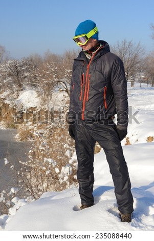 Snowboarder watching from a cliff into the valley - stock photo