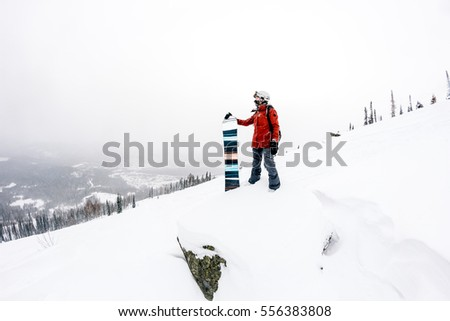 Snowboarder with snowboard in the mountains