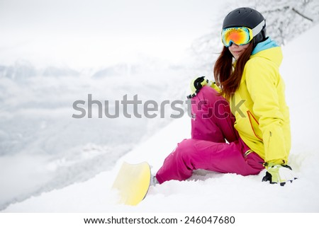 snowboarder woman sitting on snow mountain slope - stock photo
