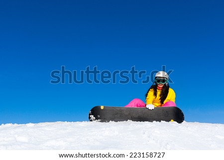 snowboarder woman sitting on snow mountain slope copy space blue sky