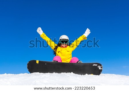 snowboarder woman sitting on snow mountain slope happy excited raised hands arms up copy space blue sky
