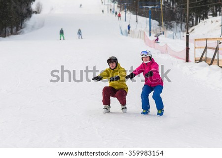 Snowboarders and skiers do warm up before exercise. Athletes crouch on the slope in winter. - stock photo