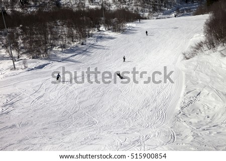 Snowboarders and skiers on ski slope at sun winter day. Caucasus Mountains. Hatsvali, Svaneti region of Georgia. View from above.