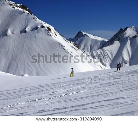 Snowboarders downhill on off piste slope at sun day. Caucasus Mountains, Georgia, ski resort Gudauri. - stock photo
