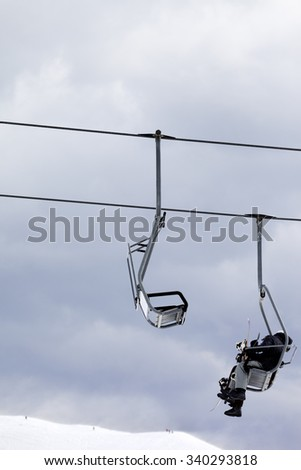 Snowboarders in chair lift at gray windy day. Caucasus Mountains, Georgia. Ski resort Gudauri. - stock photo