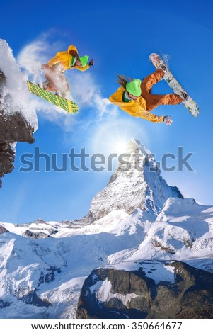 Snowboarders jumping against Matterhorn peak in Switzerland