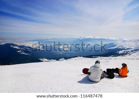 snowboarders sitting on snow and see at mountains - stock photo