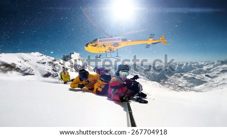 snowboarders were dropped by a helicopter at the top of the mountains while one person is taking a smile selfie with a wide angle camera.  The sun is shining brightly in the blue sky.  - stock photo