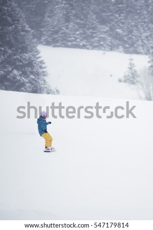 Snowboarding child with a pink helmet, blue coat and yellow pants.